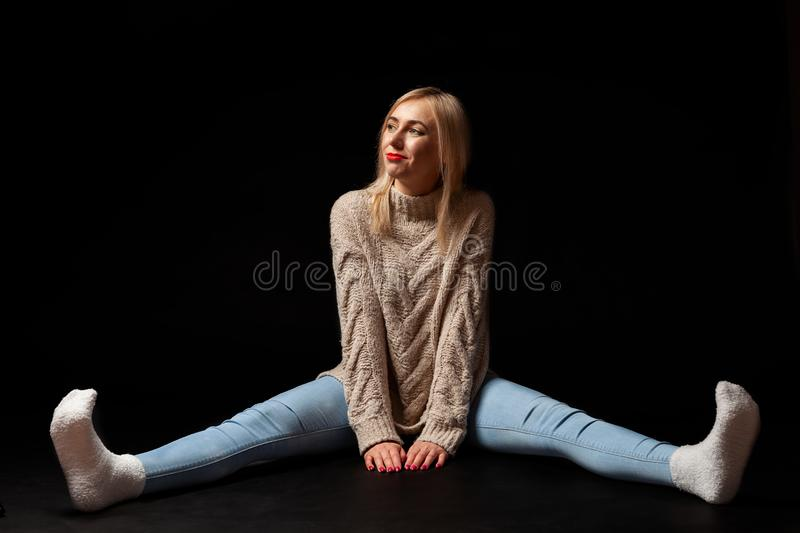 A blonde woman sits on the floor in the studio on a black background in jeans, a sweater and socks, her legs are apart, she looks stock image