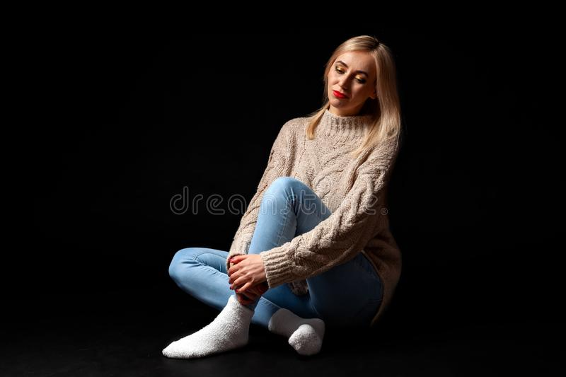 A blonde woman sits on the floor in the studio on a black background in jeans, a sweater and socks, her legs are crossed, she royalty free stock image