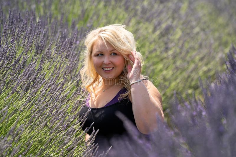 Blonde woman sits in a lavender field, looking off to the side stock photography