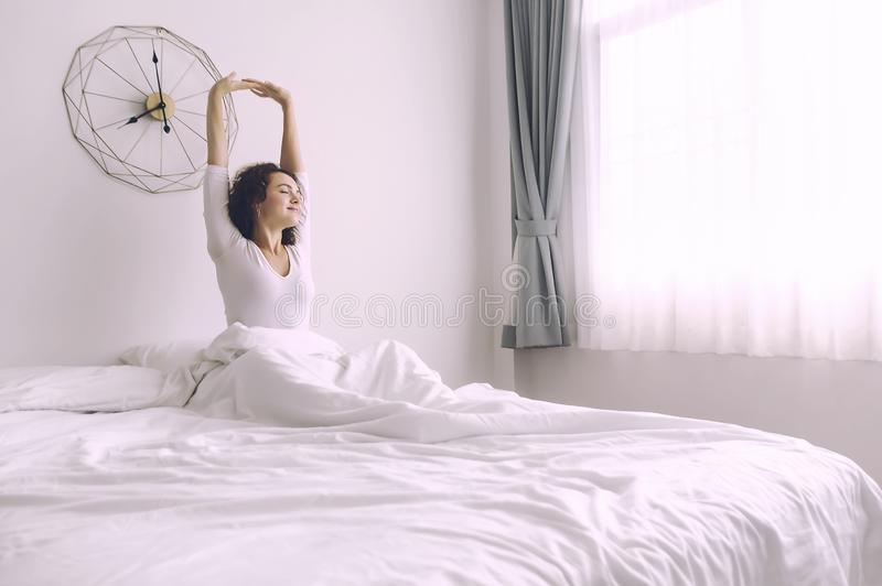 Blonde Woman sitting near the big white window while stretching on bed stock photo