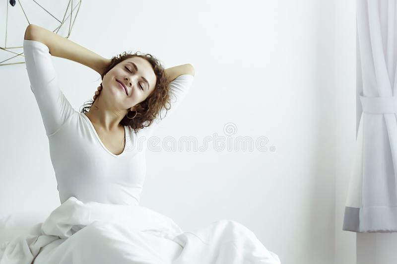 Blonde Woman sitting near the big white window while stretching on bed royalty free stock photo