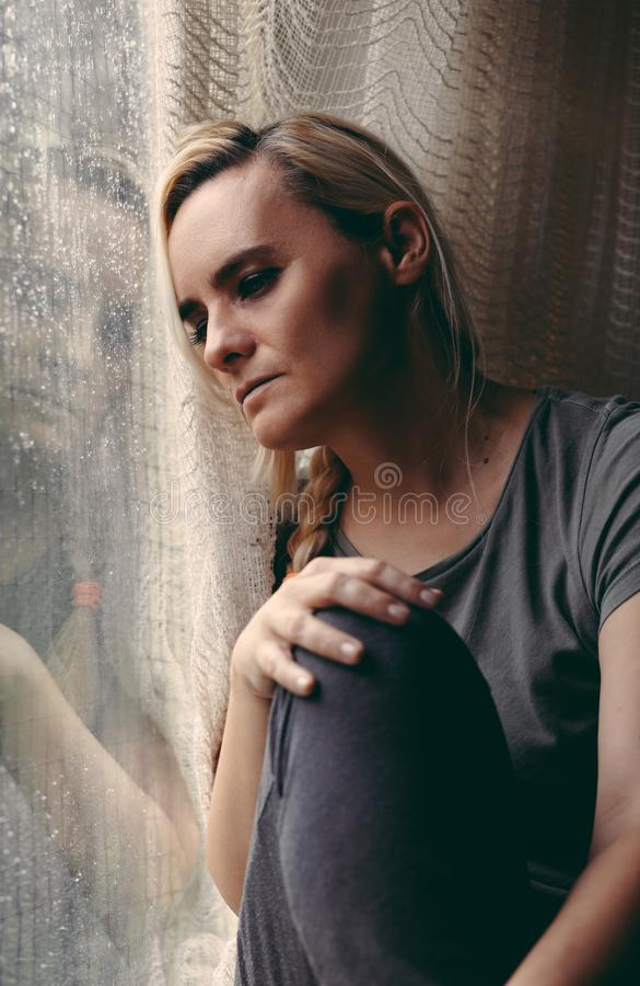 Blonde woman sitting by the rainy window, looking absently out, sad stock photos