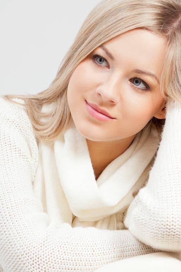 Blonde woman sitting on sofa stock image