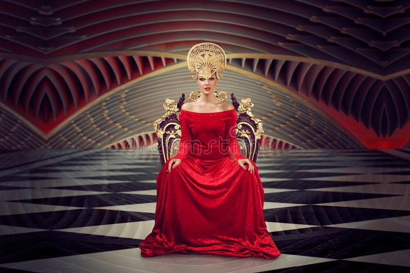 Blonde woman sitting on the throne. A woman in a luxurious gown dress sitting on a queen`s throne stock photos