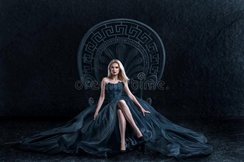 Blonde woman sitting on the throne. A woman in a luxurious gown dress sitting on a queen`s throne royalty free stock photo