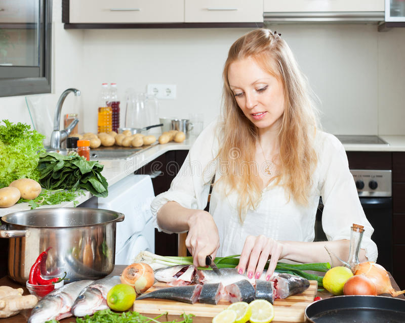 Blonde woman slicing raw fish. At kitchen table stock images