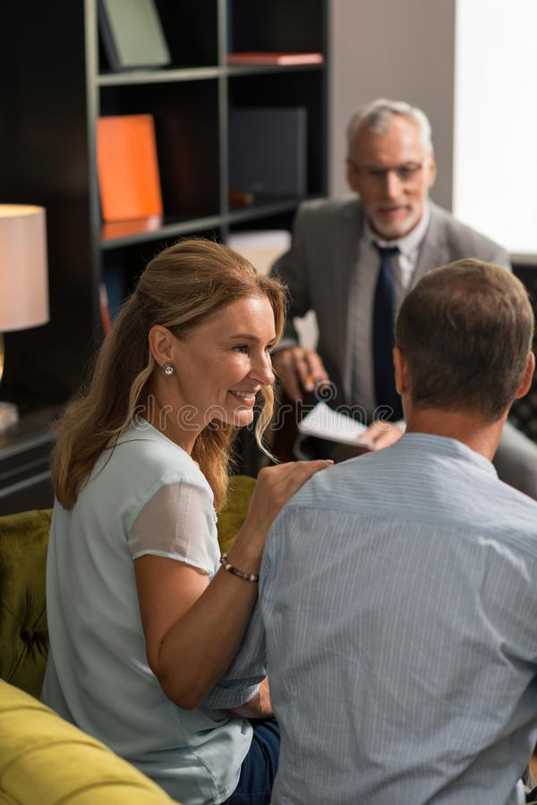 Blonde woman smiling and looking at her husband stock images