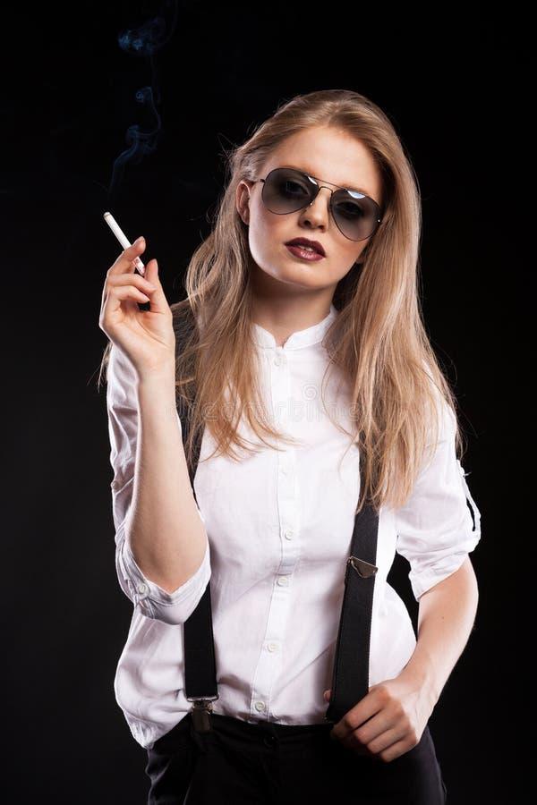 Blonde woman smoking on black background. In studio photo royalty free stock photos