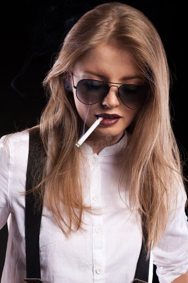 Blonde woman smoking on black background. In studio photo royalty free stock image