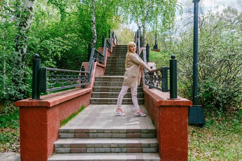 Blonde woman stands on the stairs stock image