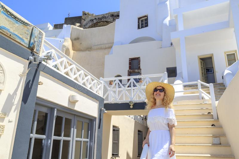 Blonde woman in streets of Thira town in Santorini, Greece royalty free stock photo
