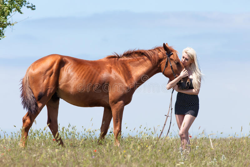 Blonde woman stroking gelding. Young blonde woman in polka-dot dress with brown horse stock image