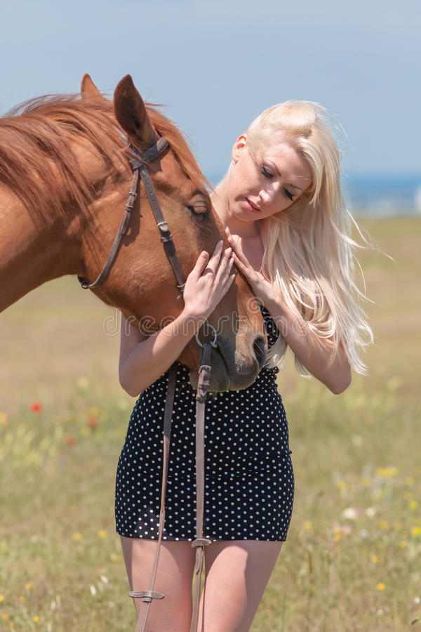 Blonde woman stroking gelding. Young blonde woman in polka-dot dress with brown horse royalty free stock image