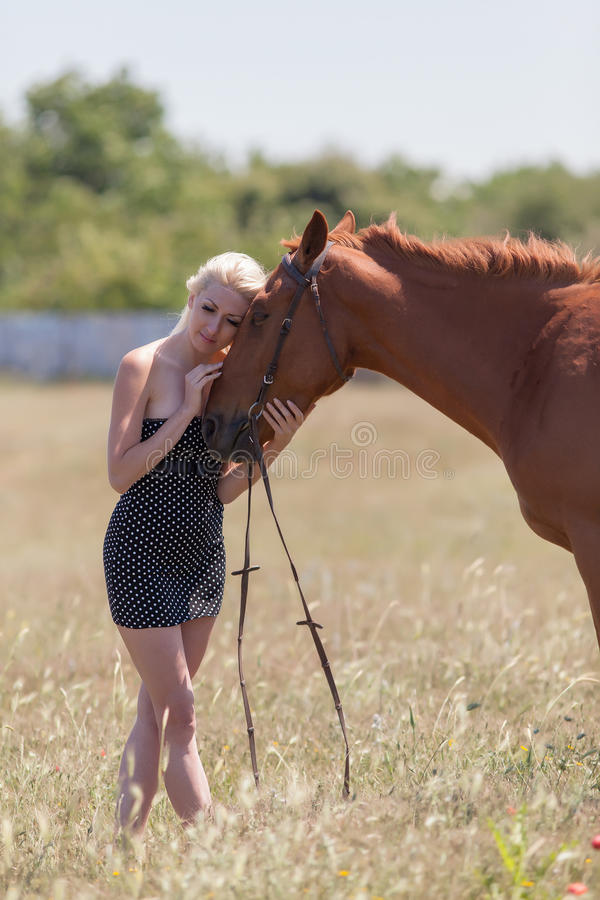 Blonde woman stroking gelding. Young blonde woman in polka-dot dress with brown horse royalty free stock images