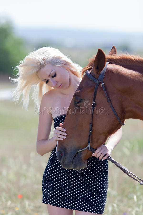 Blonde woman stroking horse. Blonde woman stroking gelding. Young blonde woman in polka-dot dress with brown horse stock photo