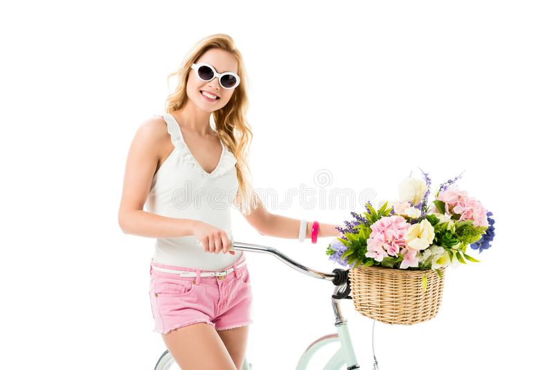 Blonde woman in sunglasses holding bicycle with flowers in basket. Isolated on white royalty free stock photography