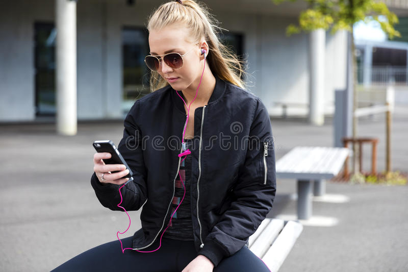 Blonde woman with sunglasses sits outdoor and uses phone. Beautiful woman with sunglasses sits on a bench in the city wearing a jacket and sportswear. Listens to royalty free stock photo