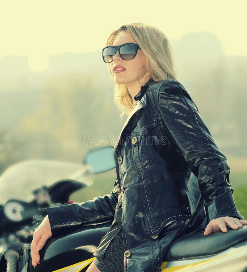Blonde woman in sunglasses on a sports motorcycle stock photo