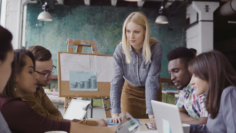 Blonde woman team leader giving direction to mixed race team of young guys. Creative business meeting at modern office. Beautiful blonde women manager giving royalty free stock photography