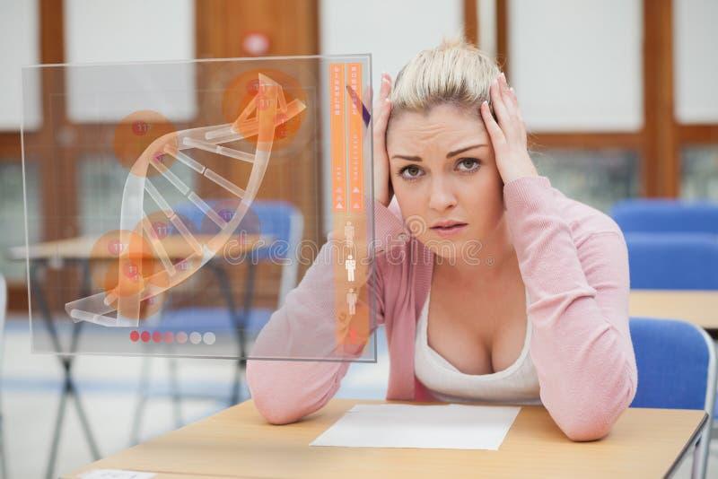 Blonde woman thinking hard while studying on interface with DNA. Blonde woman thinking hard while looking at interface with DNA on it royalty free stock image