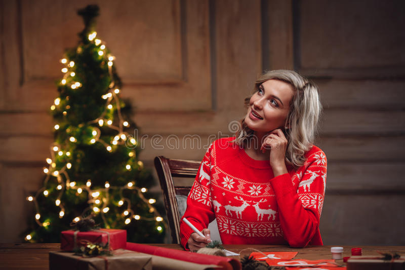 Blonde woman thinking about words on postcard royalty free stock photo