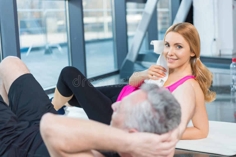Blonde woman with towel looking at camera while mature man doing abs stock image