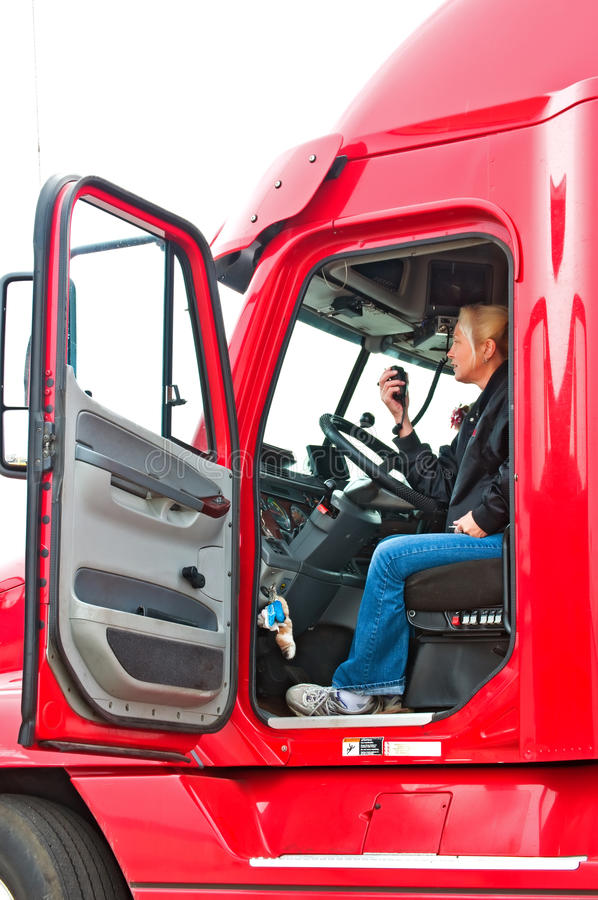 Blonde woman truck driver. Pretty blonde woman in a big rig talking on her CB radio to other truck drivers royalty free stock photography