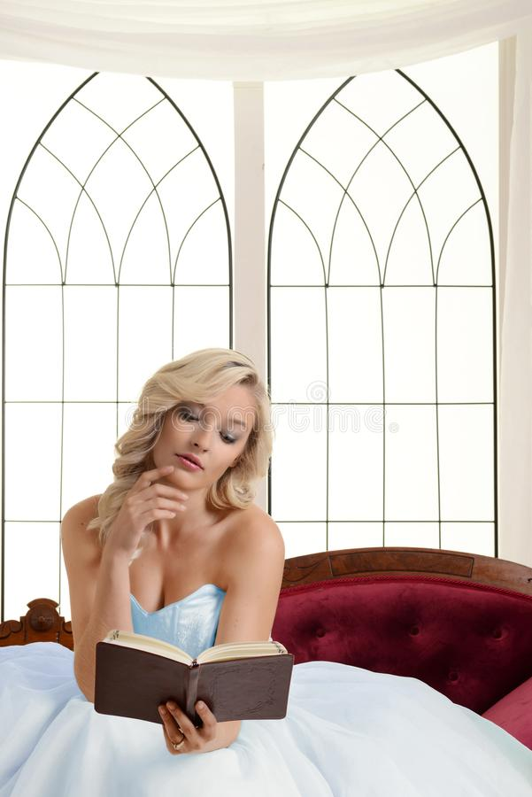 Blonde woman with tulle dress reading book on couch royalty free stock image