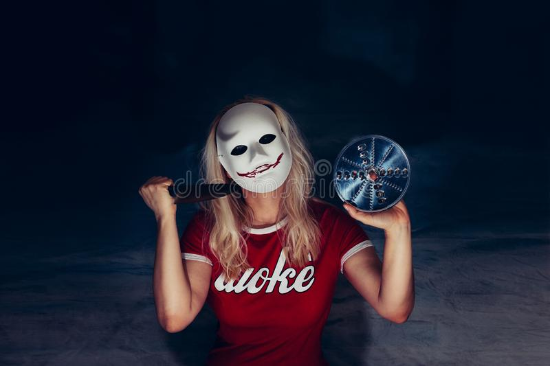 Blonde woman under white mask with spooky bloody smile, holding knife royalty free stock photos
