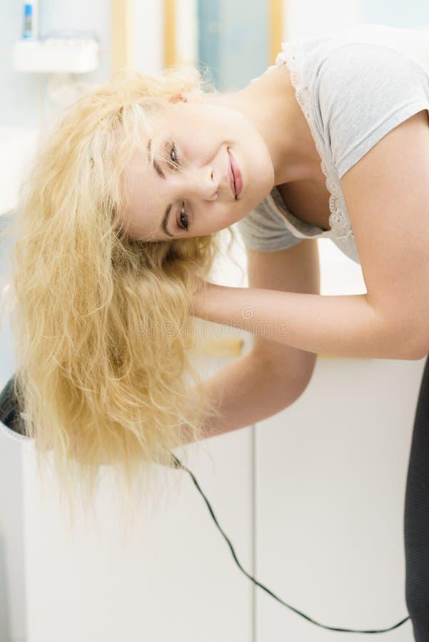 Blonde woman using hair dryer stock photos