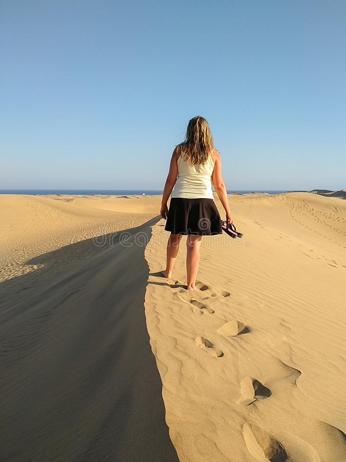 blonde woman walking at the top of a dune while looking the sea on the horizon at the sunset. Walking the barefoot girl is shaping royalty free stock photo