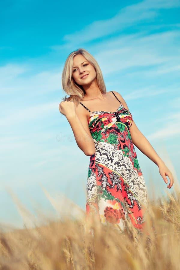 Blonde woman walking on wheat field stock photo