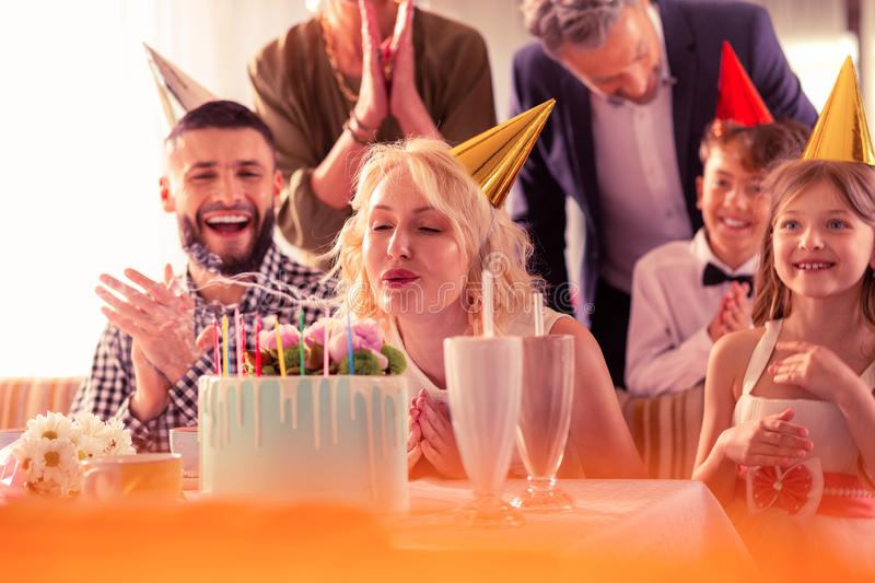 Blonde woman with wavy hair blowing candles on birthday cake stock photo