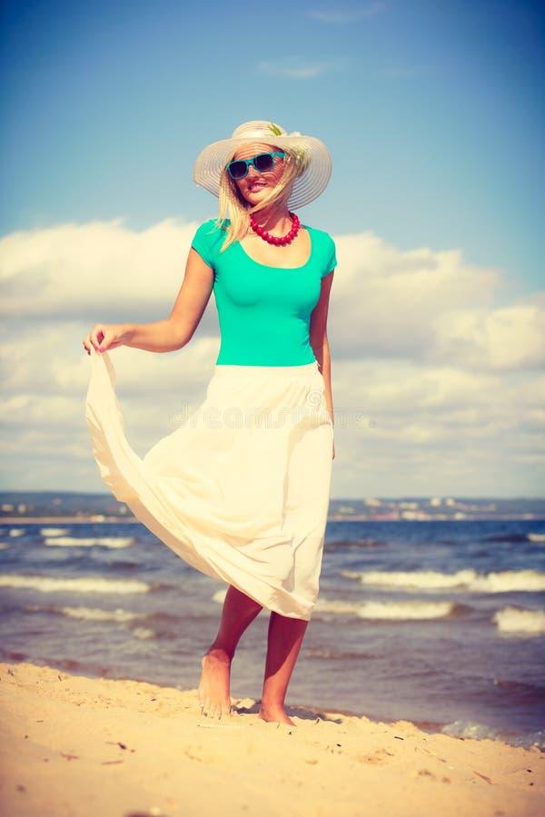 Blonde woman wearing dress walking on beach stock photography