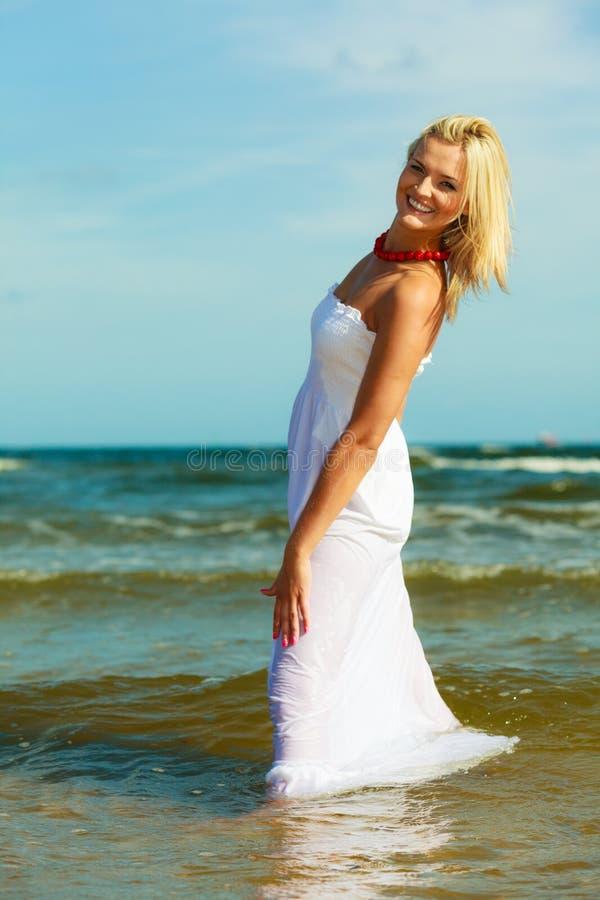 Blonde woman wearing dress walking in water royalty free stock images