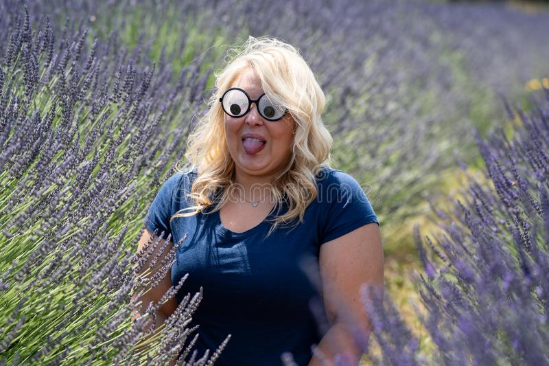 Blonde woman wearing googly eyes novelty sunglasses while sitting in a field of lavender, looking surprised with her tounge stock photography