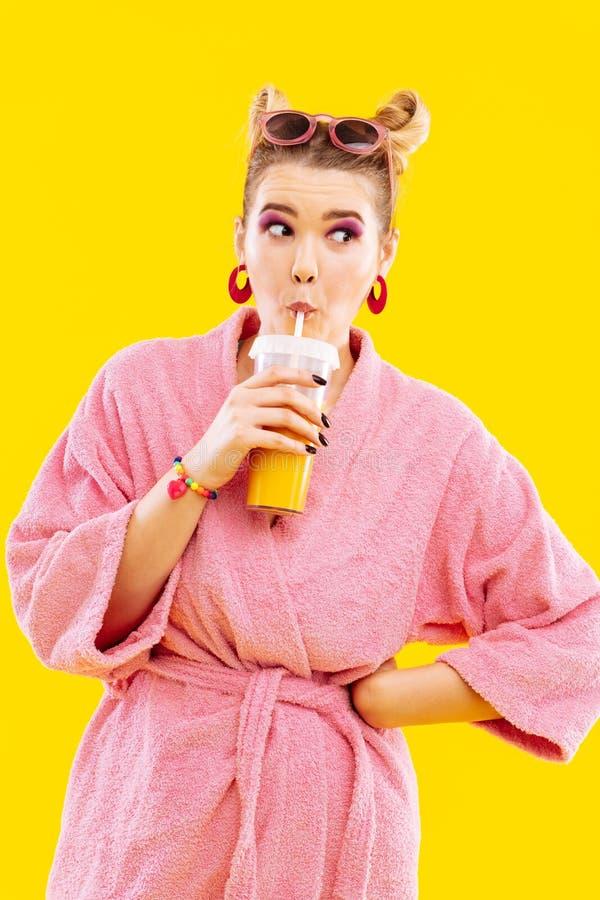 Blonde woman wearing pink bathrobe drinking morning juice. Morning juice. Blonde-haired woman wearing pink bathrobe and sunglasses drinking morning juice stock image