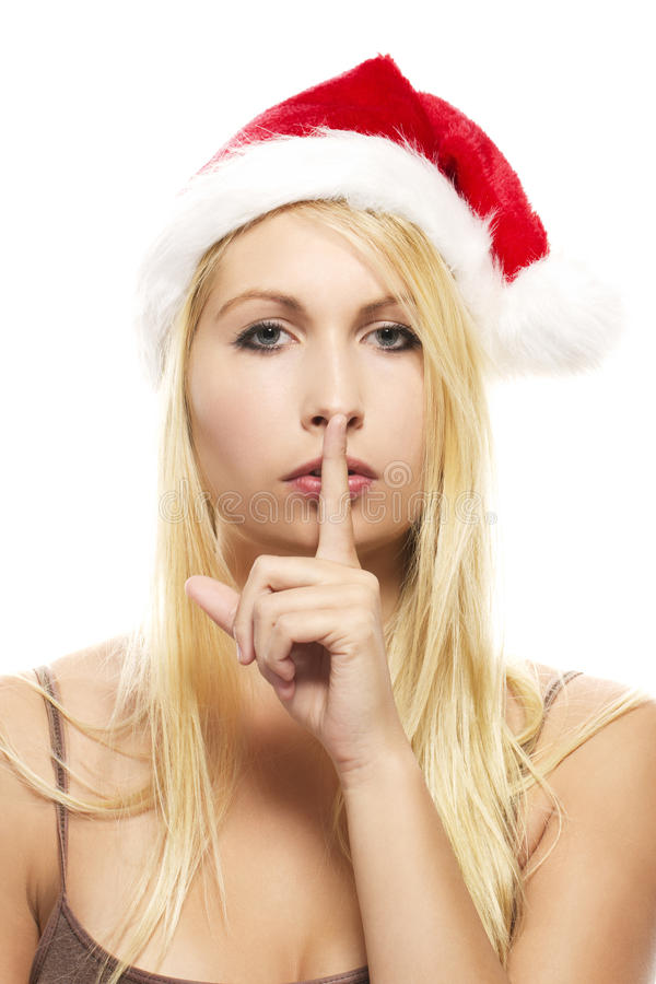 Blonde woman wearing santa's hat putting stock image