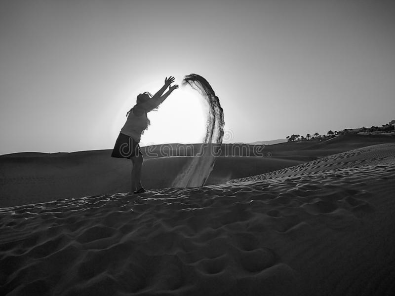 Blonde woman wearing skirt launching sand of the desert from the floor to the air a sunset. When she trows the sand it describes a. Curve before falling. Many stock image