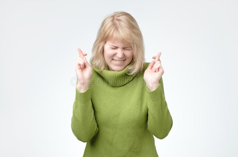 Blonde woman wears green sweater, smiles broadly, keeps fingers crossed, hopes for good luck. Glad happy blonde woman wears green sweater, smiles broadly, keeps stock photography