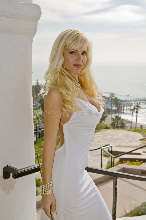 Blonde Woman in White Dress. With Pier in the background stock photo