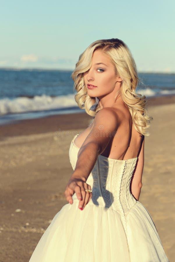 Blonde woman in white dress follow me on beach stock photo