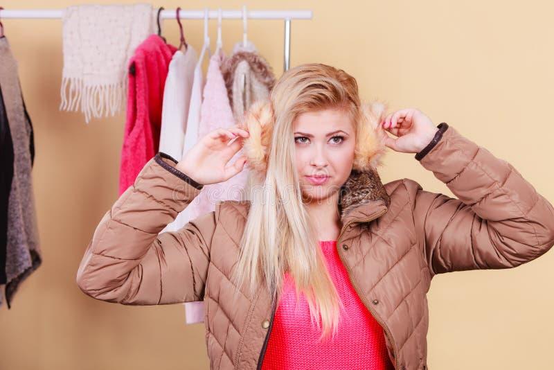 Blonde woman in winter warm earmuffs stock photography