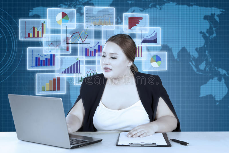 Blonde woman works on laptop and clipboard royalty free stock image