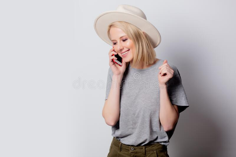 Blonde womanin hat using mobile phone on white background royalty free stock images