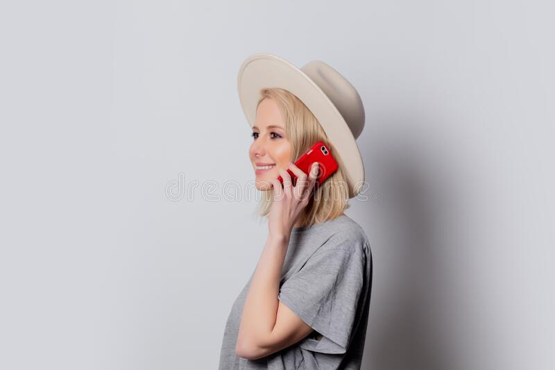 Blonde womanin hat using mobile phone on white background stock images