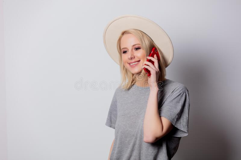Blonde womanin hat using mobile phone on white background royalty free stock photo
