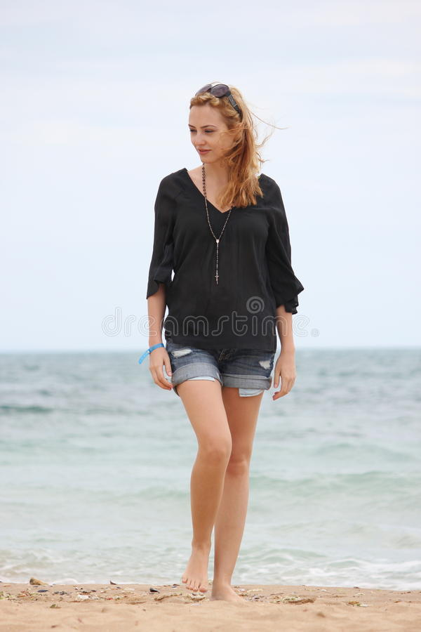 Blonde Women in black shirt. Young blonde women dreesed in black shirt at the beach royalty free stock photo