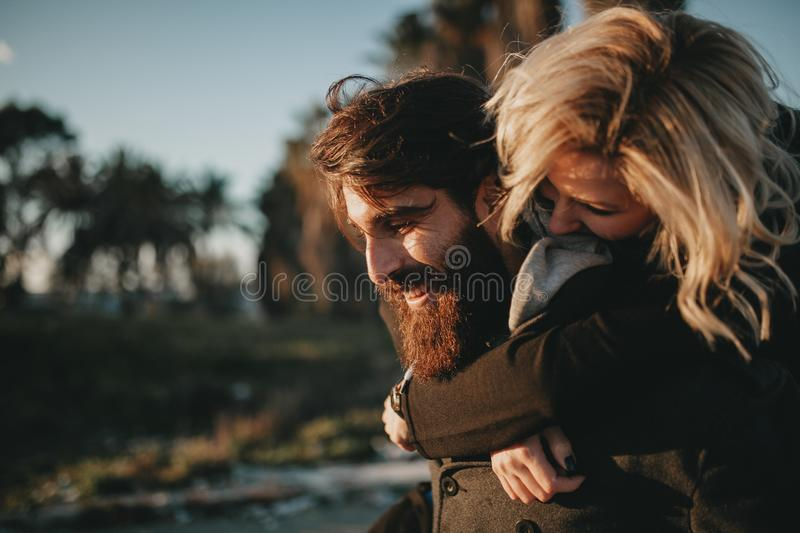 Cool indie couple having fun outdoors while he gives her a piggyback. stock photography