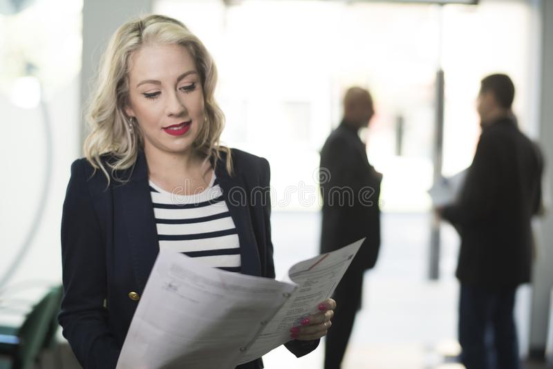 Blonde woman in office looking papers stock image